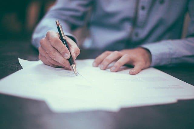 Qué es la referencia del SigPac - persona escribiendo sobre unos documentos en blanco